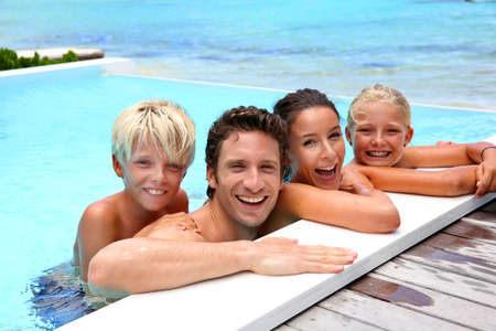 pool deck: Family of four bathing in swimming pool