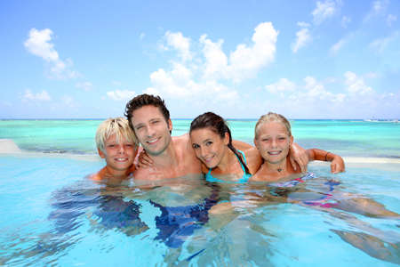 guadeloupe: Family of four bathing in swimming pool