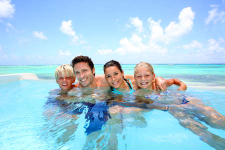 femme baignoire: Famille de quatre baignade dans la piscine