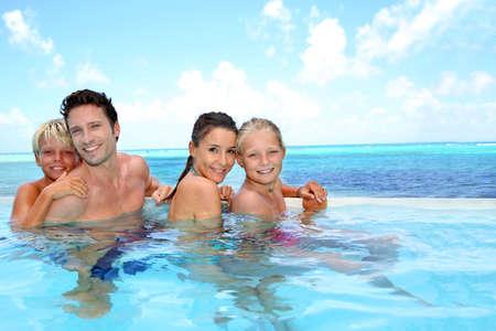 niños nadando: Familia de cuatro ba?arse en la piscina