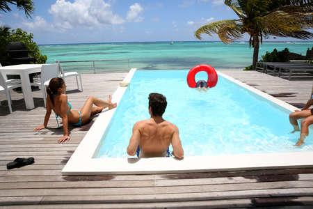 hanging around: Familia que cuelga alrededor de la piscina de borde infinito por el mar