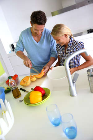 Man with young girl preparing meal in kitchen photo