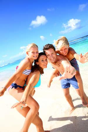 familia viaje: Familia de cuatro personas que se divierten en la playa Foto de archivo