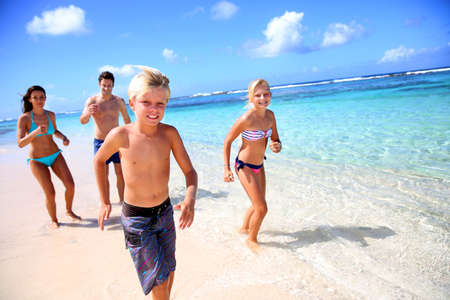 Family running on a paradisaical beach photo