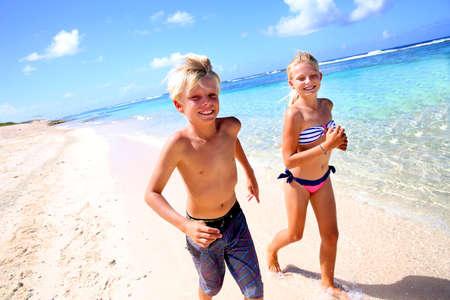 child bikini: Kids running on a sandy beach in Caribe Stock Photo