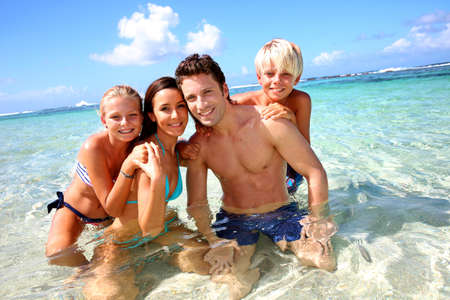 bikini couple: Couple and children in crystal clear water Stock Photo