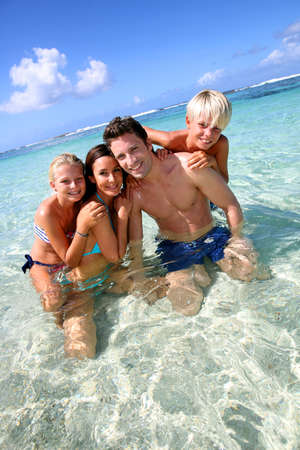 Couple and children in crystal clear water photo