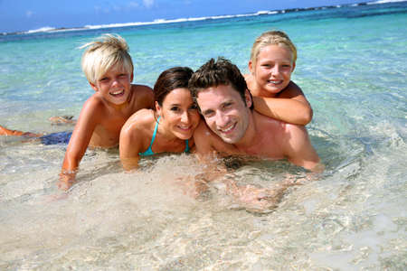 vacation beach: Couple and children in crystal clear water Stock Photo