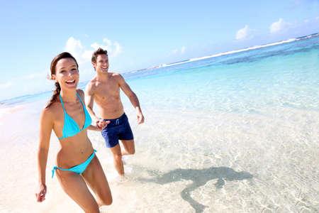 traje de bano: Pares que se ejecutan en una playa de arena