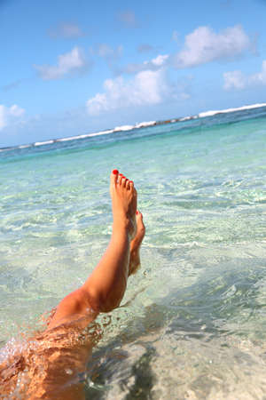 Closeup of womans feet in Caribbean sea photo