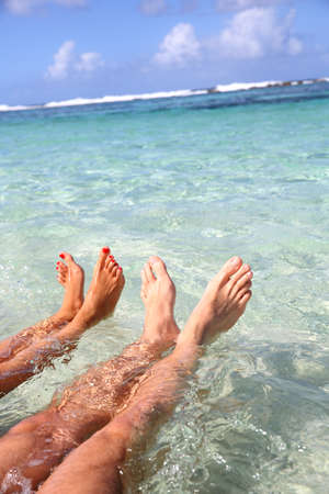beach feet: Closeup of couples feet in lagoon water