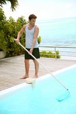 pool deck: Swimming-pool service man cleaning water