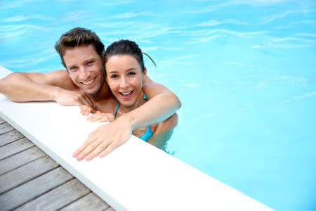 Portrait of cheerful couple in swimming-pool photo