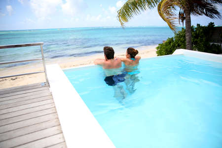 hotel resort: Couple looking at the sea from swimming-pool
