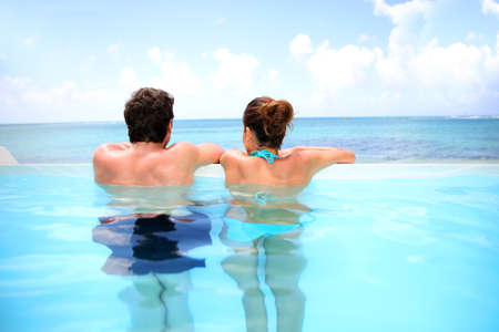 bikini pool: Couple looking at the sea from swimming-pool
