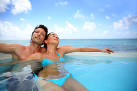 Couple relaxing in swimming pool photo