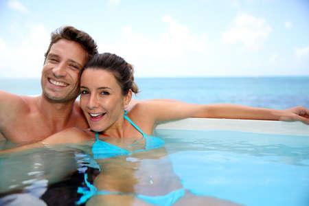 infinity pool: Couple having fun in swimming-pool Stock Photo