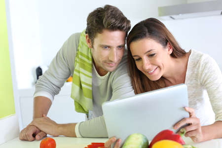 Couple in home kitchen looking for lunch recipe photo
