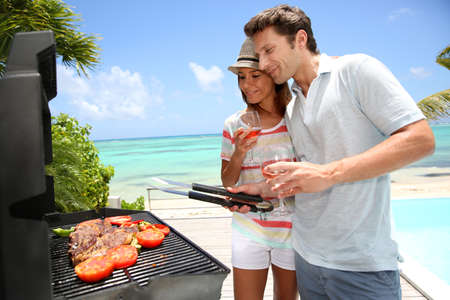 pool party: Cheerful couple in holidays preparing grilled meat