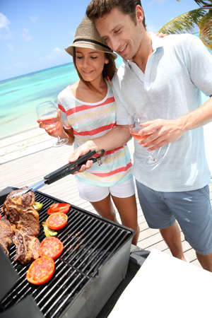 caribe: Cheerful couple in holidays preparing grilled meat