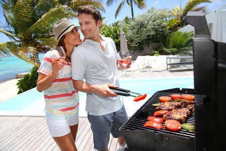 pool deck: Cheerful couple in holidays preparing grilled meat