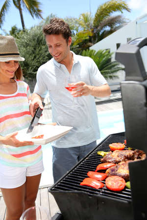 party hat: Cheerful couple in holidays preparing grilled meat