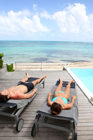 seaview: Couple relaxing in long chairs in front of the sea