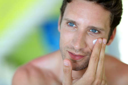 DERMATOLOGY: Handsome man applying moisturizing cream Stock Photo