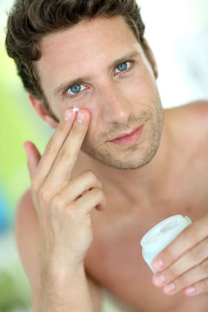Handsome man applying moisturizing cream photo