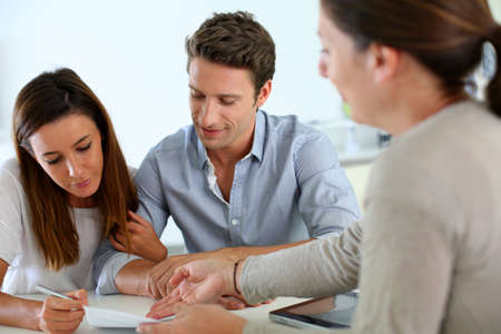 financial advisor: Couple signing real-estate contract Stock Photo