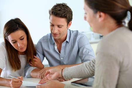 firmando: Pareja de firmar el contrato de bienes raíces