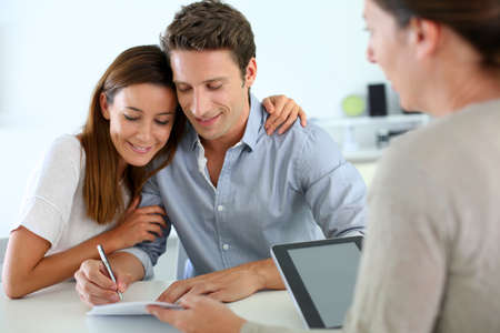 signing a contract: Couple signing real-estate contract Stock Photo