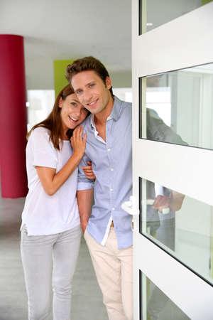 abriendo puerta: Pareja alegre invitando a la gente a entrar en la casa