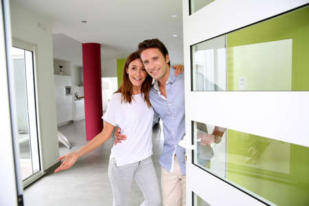 inviting: Cheerful couple inviting people to enter in home