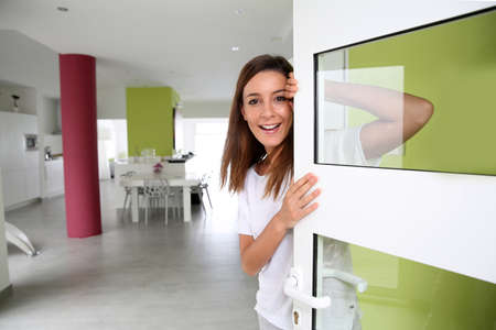 puerta: Mujer joven bienvenida a la gente en la puerta de entrada