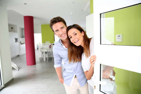 front door: Cheerful couple inviting people to enter in home