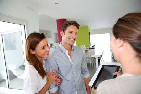 realestate: Couple visiting home with real-estate agent