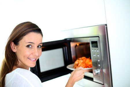 oven: Woman putting plate in microwave oven Stock Photo
