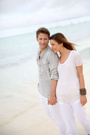 Romantic couple walking on the beach photo