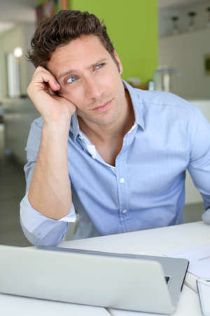Man in front of laptop with upset look Stock Photo - 19376260