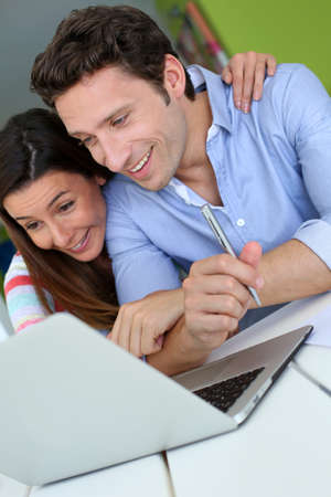Couple at home sitting in front of laptop Stock Photo - 19376259