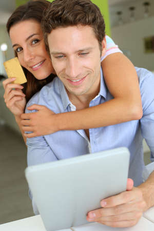 Cheerful couple with tablet shopping on internet photo