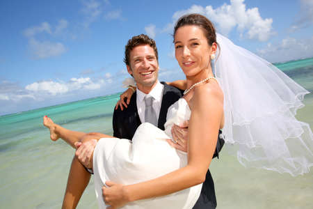 Groom holding his bride by the Caribbean sea photo