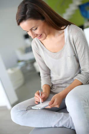 30 years old woman: Woman at home relaxing and using smartphone Stock Photo