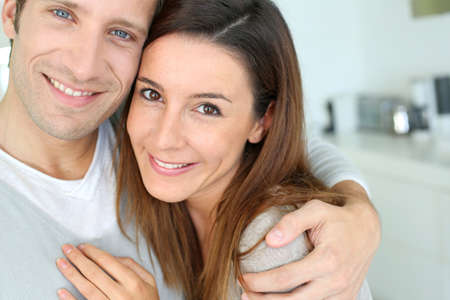 Portrait of cheerful couple standing at home photo