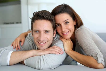 30 years old married couple: Portrait of sweet couple sitting in sofa