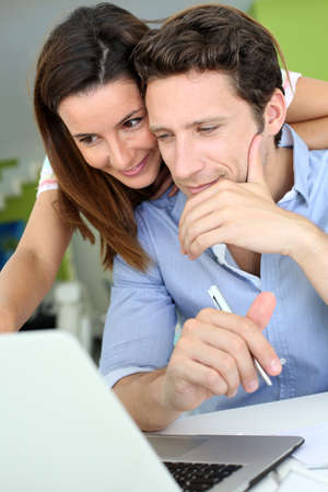 Couple at home looking at bank account on internet photo