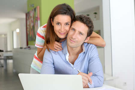 cuenta bancaria: Pareja en casa mirando la cuenta bancaria en internet