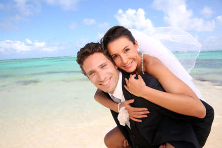 Groom carrying bride on his back at the beach photo