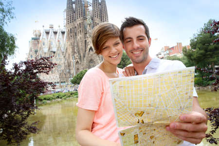 Couple reading map in front of the Sagrada familia church Stock Photo